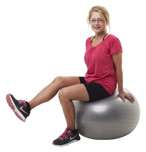 older adult woman doing leg exercises on a fit ball